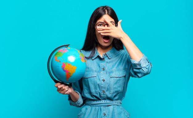 Jonge spaanse vrouw die geschokt, bang of doodsbang kijkt, haar gezicht bedekt met de hand en tussen de vingers gluurt. aarde planeet concept