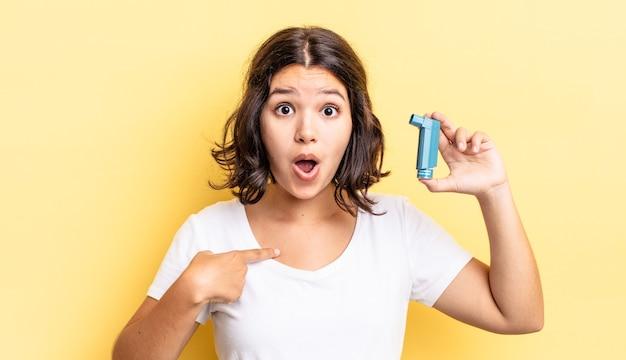 Jonge spaanse vrouw die geschokt en verrast kijkt met wijd open mond, wijzend naar zichzelf. astma concept