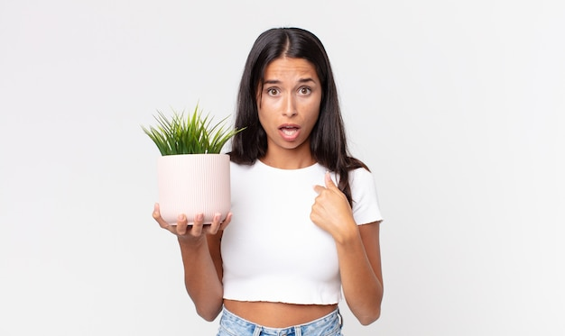 Jonge spaanse vrouw die geschokt en verrast kijkt met wijd open mond, wijzend naar zichzelf en een decoratieve kamerplant vasthoudend