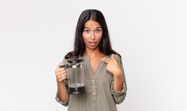 Jonge spaanse vrouw die geschokt en verrast kijkt met wijd open mond, wijzend naar zichzelf en een handmatig koffiezetapparaat vasthoudend