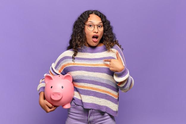 Jonge spaanse vrouw die geschokt en verrast kijkt met wijd open mond, wijzend naar zichzelf. spaarvarken concept