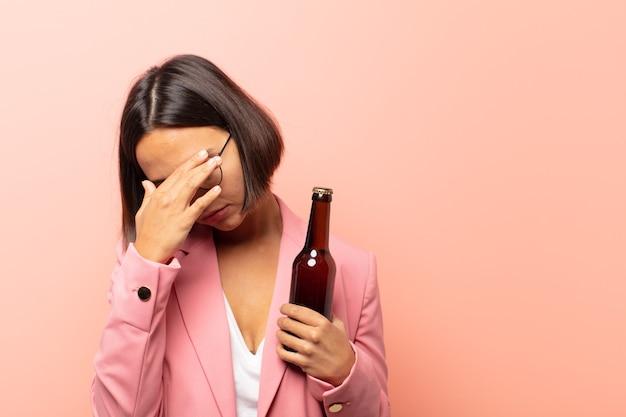 Jonge spaanse vrouw die gestrest, beschaamd of boos kijkt, met hoofdpijn, gezicht bedekt met hand