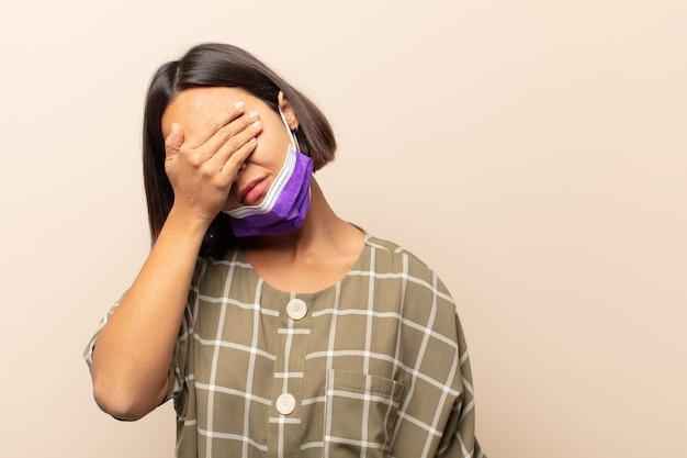 Jonge spaanse vrouw die gestrest, beschaamd of overstuur kijkt, met hoofdpijn, gezicht bedekt met hand