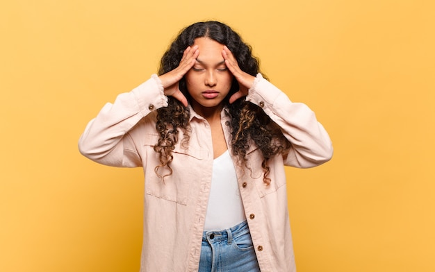 Jonge spaanse vrouw die gestrest en gefrustreerd kijkt, onder druk werkt met hoofdpijn en last heeft van problemen