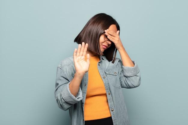 Jonge spaanse vrouw die gezicht bedekt met hand en andere hand naar voren zet om de camera te stoppen, foto's of afbeeldingen weigeren