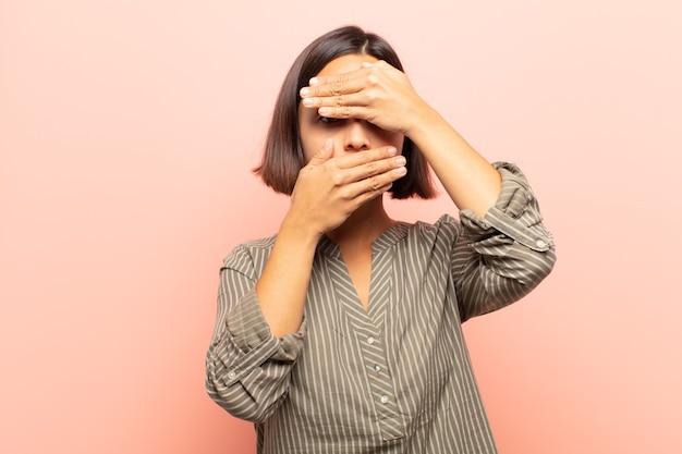 Jonge spaanse vrouw die gezicht behandelt met beide handen die nee zeggen tegen de camera! afbeeldingen weigeren of foto's verbieden