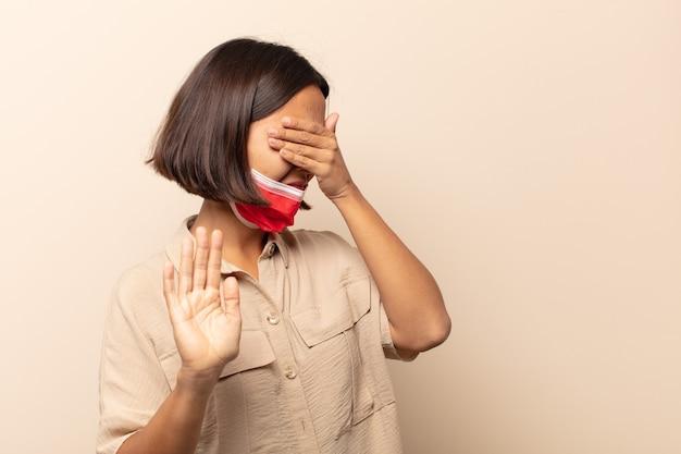 Jonge spaanse vrouw die gezicht behandelt met hand en andere hand vooraan zet