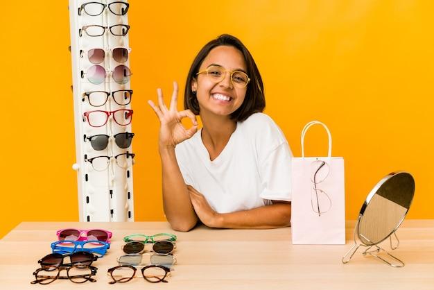 Jonge spaanse vrouw die glazen geïsoleerd vrolijk en zelfverzekerd probeert te tonen die ok gebaar toont.
