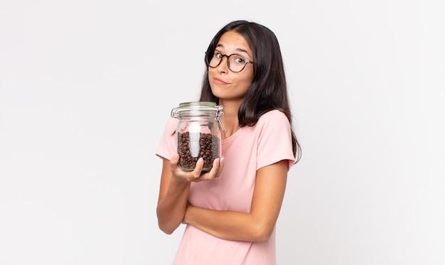 Jonge spaanse vrouw die haar schouders ophaalt, zich verward en onzeker voelt en een fles koffiebonen vasthoudt