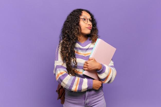 Jonge spaanse vrouw die haar schouders ophaalt, zich verward en onzeker voelt, twijfelt met gekruiste armen en een verbaasde blik. student concept