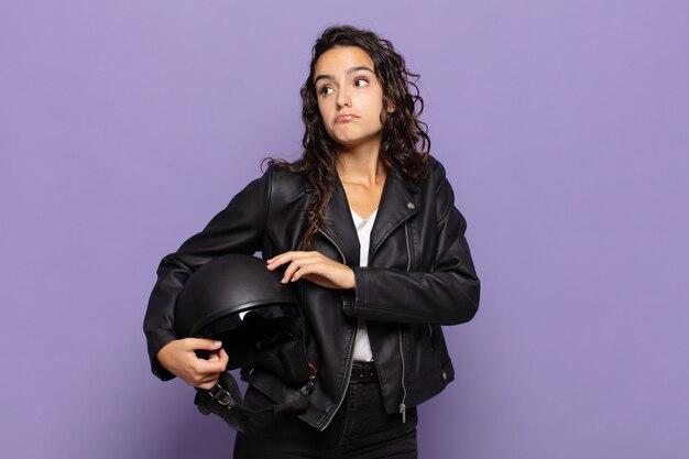 Jonge spaanse vrouw die haar schouders ophaalt, zich verward en onzeker voelt, twijfelt met gekruiste armen en een verbaasde blik