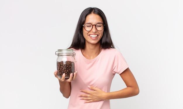Jonge spaanse vrouw die hardop lacht om een hilarische grap en een fles koffiebonen vasthoudt