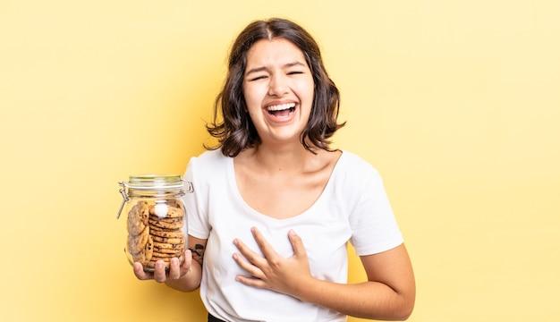 Jonge spaanse vrouw die hardop lacht om een hilarische grap. koekjes fles concept
