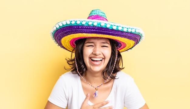 Jonge spaanse vrouw die hardop lacht om een hilarische grap. mexicaanse hoed concept