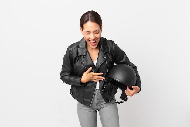 Jonge spaanse vrouw die hardop lacht om een hilarische grap. motorrijder concept