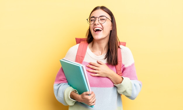 Jonge spaanse vrouw die hardop lacht om een hilarische grap. studentenconcept