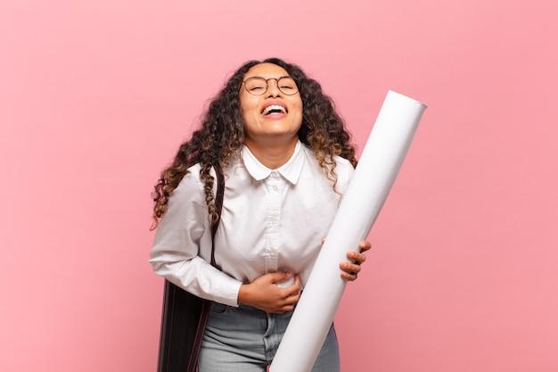 Jonge spaanse vrouw die hardop lacht om een hilarische grap, zich gelukkig en opgewekt voelt, plezier heeft. architect concept