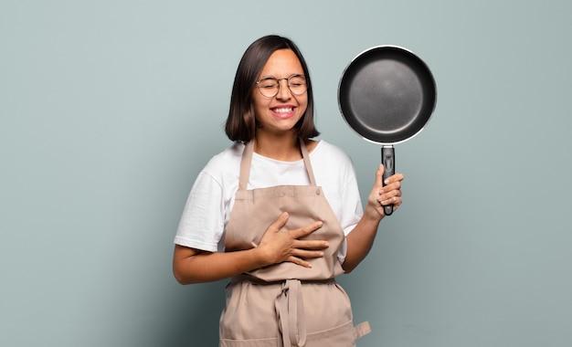 Jonge spaanse vrouw die hardop lacht om een hilarische grap, zich gelukkig en opgewekt voelt, plezier heeft