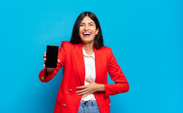 Jonge spaanse vrouw die hardop lacht om een of andere hilarische grap, zich gelukkig en opgewekt voelt, lol heeft