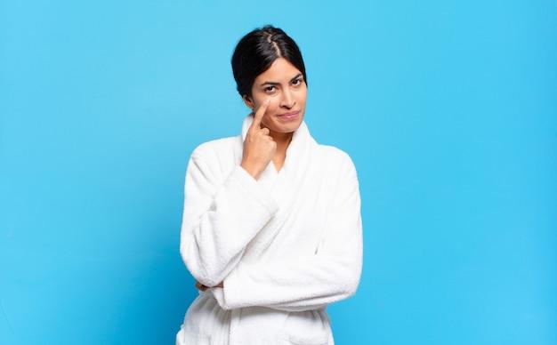 Jonge spaanse vrouw die je in de gaten houdt, niet vertrouwt, kijkt en alert en waakzaam blijft. badjas concept