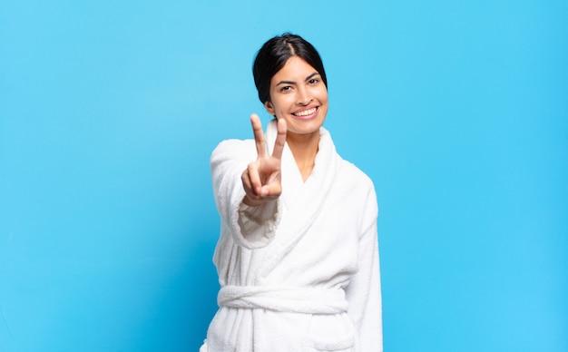 Jonge spaanse vrouw die lacht en er gelukkig, zorgeloos en positief uitziet, gebarend overwinning of vrede met één hand. badjas concept