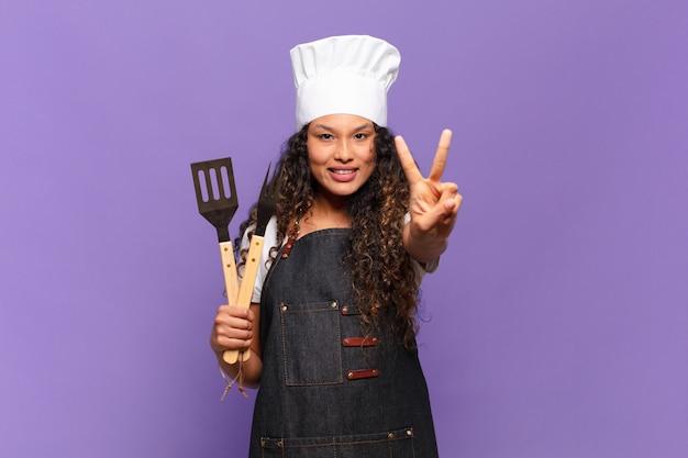 Jonge spaanse vrouw die lacht en er gelukkig, zorgeloos en positief uitziet, gebarend overwinning of vrede met één hand. barbecue chef-kok concept