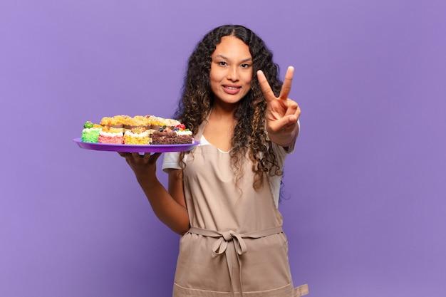 Jonge spaanse vrouw die lacht en er gelukkig, zorgeloos en positief uitziet, gebarend overwinning of vrede met één hand. koken taarten concept