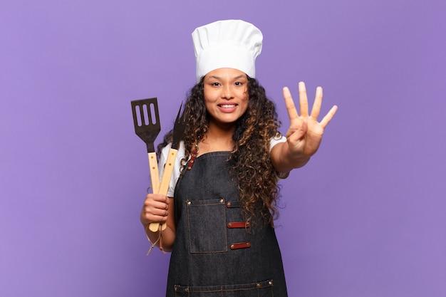 Jonge spaanse vrouw die lacht en er vriendelijk uitziet, met nummer vier of vierde met de hand naar voren, aftellend. barbecue chef-kok concept