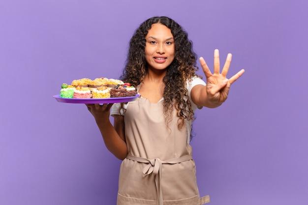 Jonge spaanse vrouw die lacht en er vriendelijk uitziet, met nummer vier of vierde met de hand naar voren, aftellend. koken taarten concept