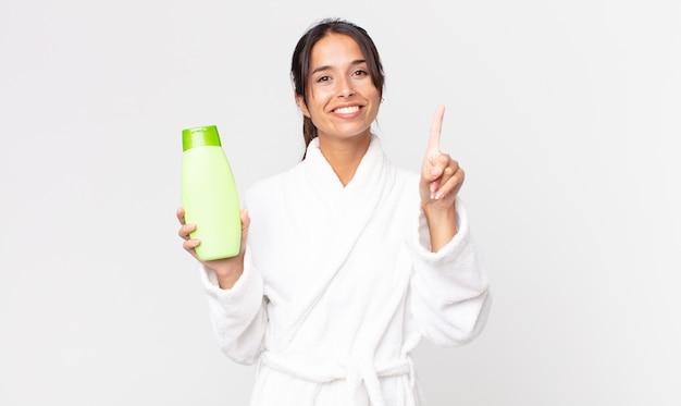 Jonge spaanse vrouw die lacht en er vriendelijk uitziet, nummer één laat zien die een badjas draagt en een shampoo vasthoudt
