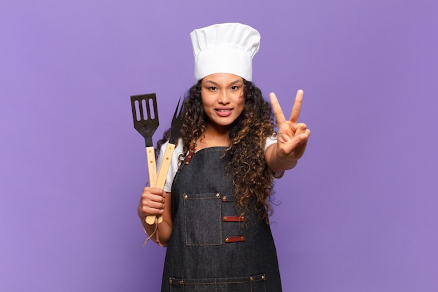 Jonge spaanse vrouw die lacht en er vriendelijk uitziet, nummer twee of seconde toont met de hand naar voren, aftellend. barbecue chef-kok concept