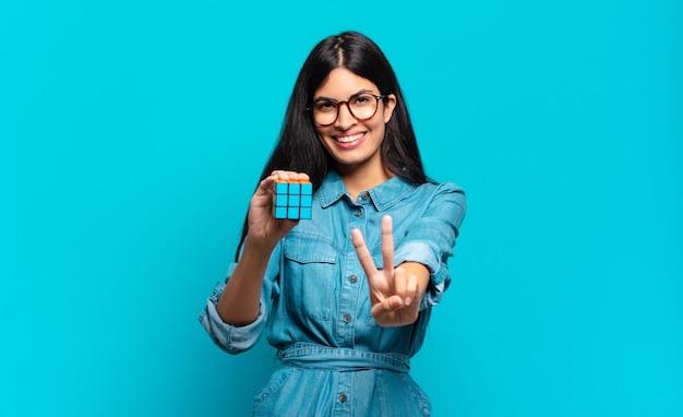 Jonge spaanse vrouw die lacht en er vriendelijk uitziet, nummer twee of seconde toont met de hand naar voren, aftellend. intelligentie probleem concept