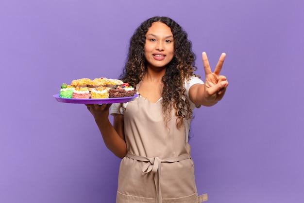 Jonge spaanse vrouw die lacht en er vriendelijk uitziet, nummer twee of seconde toont met de hand naar voren, aftellend. koken taarten concept