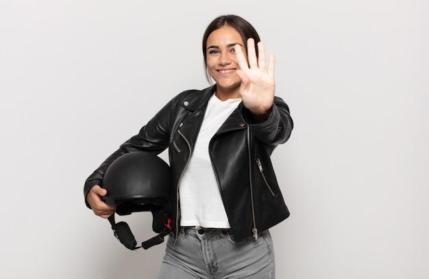 Jonge spaanse vrouw die lacht en er vriendelijk uitziet, nummer vier of vierde toont met de hand naar voren, aftellend
