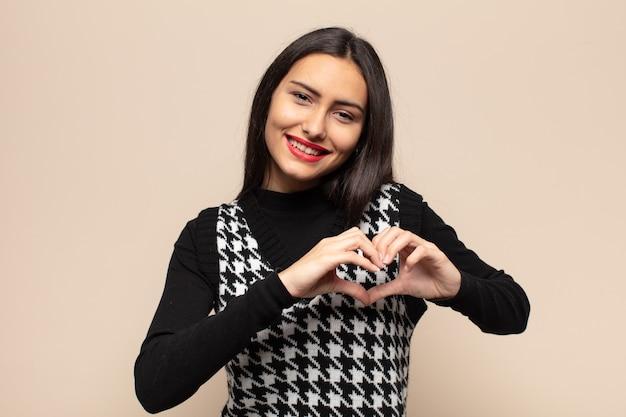 Jonge spaanse vrouw die lacht en zich gelukkig, schattig, romantisch en verliefd voelt, hartvorm maakt met beide handen
