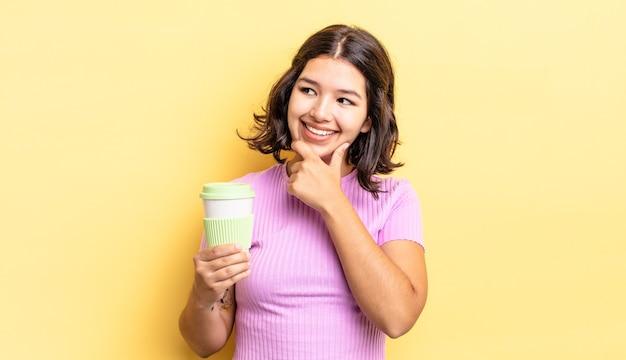 Jonge spaanse vrouw die lacht met een gelukkige, zelfverzekerde uitdrukking met de hand op de kin. afhaal koffie concept