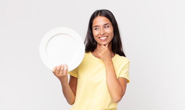 Jonge spaanse vrouw die lacht met een gelukkige, zelfverzekerde uitdrukking met de hand op de kin en een leeg bord vasthoudt