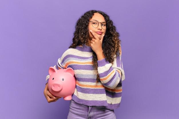 Jonge spaanse vrouw die lacht met een gelukkige, zelfverzekerde uitdrukking met de hand op de kin, zich afvragend en opzij kijkend. spaarvarken concept