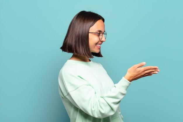 Jonge spaanse vrouw die lacht, u begroet en een handschud aanbiedt om een succesvolle overeenkomst, samenwerkingsconcept te sluiten