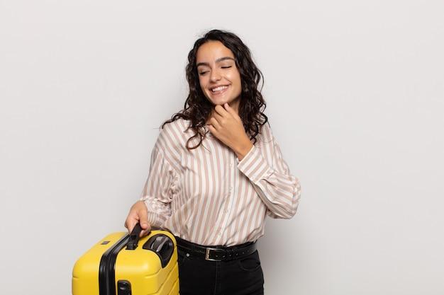 Jonge spaanse vrouw die met een gelukkige, zekere uitdrukking glimlacht met hand op kin, zich afvraagt en naar de kant kijkt