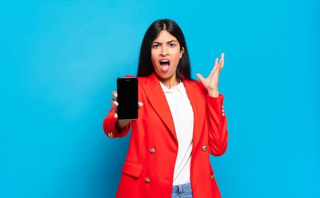 Jonge spaanse vrouw die met handen in de lucht gilt, zich woedend, gefrustreerd, gestrest en boos voelt. telefoon scherm kopie ruimte