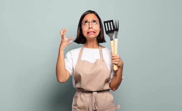 Jonge spaanse vrouw die met handen in de lucht gilt, zich woedend, gefrustreerd, gestrest en boos voelt