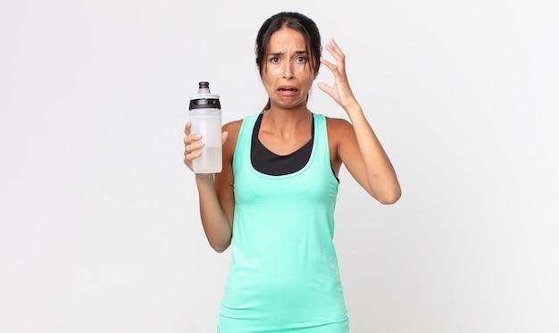 Jonge spaanse vrouw die met handen in de lucht schreeuwt en een waterfles vasthoudt. fitnessconcept