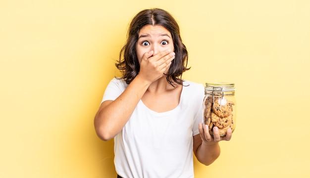 Jonge spaanse vrouw die mond bedekt met handen met een geschokt. koekjes fles concept
