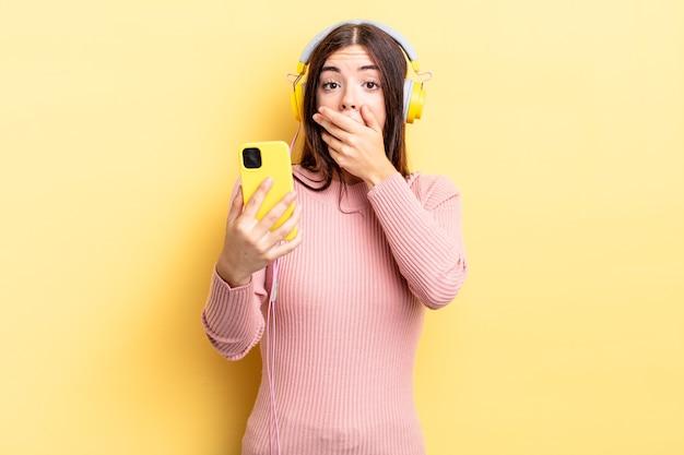 Jonge spaanse vrouw die mond bedekt met handen met een geschokt. koptelefoon en telefoon concept