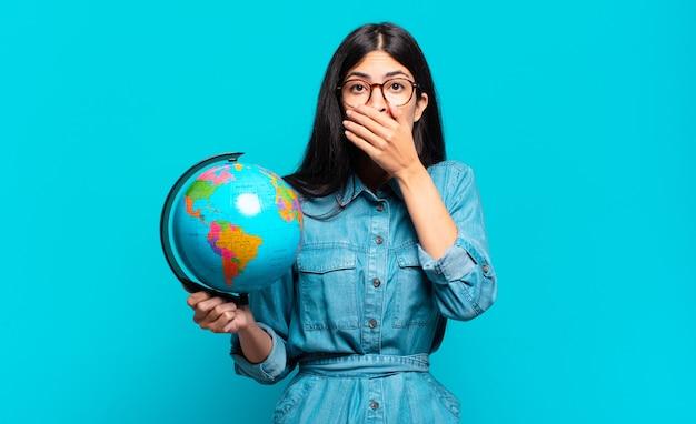 Jonge spaanse vrouw die mond bedekt met handen met een geschokte, verbaasde uitdrukking, een geheim bewaren of oeps zeggen. aarde planeet concept