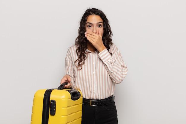 Jonge spaanse vrouw die mond bedekt met handen met een geschokte, verbaasde uitdrukking, een geheim bewaren of oeps zeggen
