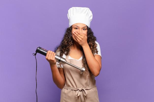 Jonge spaanse vrouw die mond bedekt met handen met een geschokte, verbaasde uitdrukking, een geheim houdt of oeps zegt. chef-kok concept