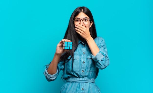 Jonge spaanse vrouw die mond bedekt met handen met een geschokte, verbaasde uitdrukking, een geheim houdt of oeps zegt. intelligentie probleem concept
