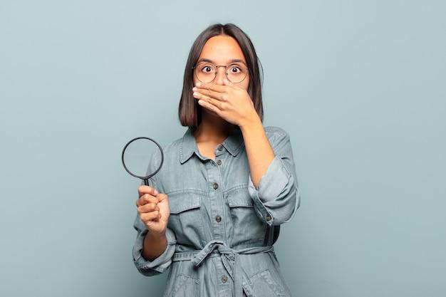 Jonge spaanse vrouw die mond bedekt met handen met een geschokte, verbaasde uitdrukking, een geheim houdt of oeps zegt saying